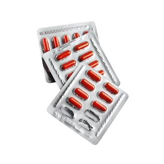 Rode pillencapsules in blaarpakken die op wit worden geïsoleerd