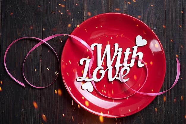 Rode plaat met houten letters met liefde op een houten achtergrond, bovenaanzicht