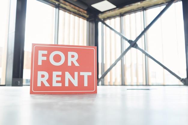 Rode plakkaat staat op de vloer in lege kantoorruimte deze ruimte is te huur