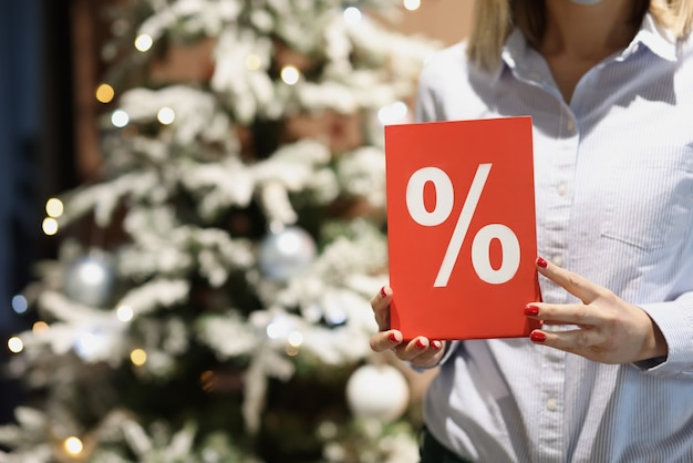 Rode plaquette met procent in vrouwelijke handen van de verkoper tegen de achtergrond van de kerstboom van het nieuwe jaar