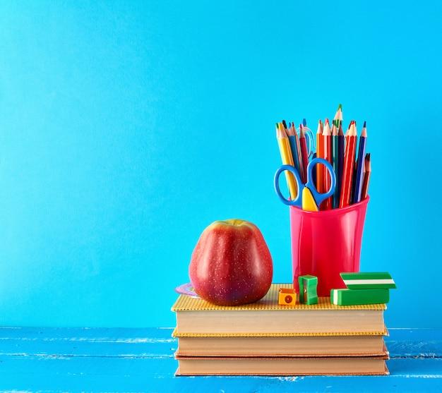 Rode plastic beker met veelkleurige houten potloden staat op een stapel boeken