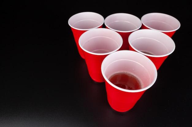 Rode plastic bekers en bal voor een spelletje bier pong