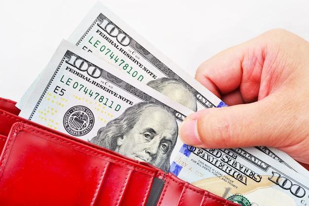 Rode portemonnee met amerikaanse dollars in de handen op een witte achtergrond