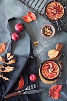 Rode pruimen en pruimentaartjes in gietijzeren koekenpannen op een zwarte keukenschort die op grijs wordt geworpen