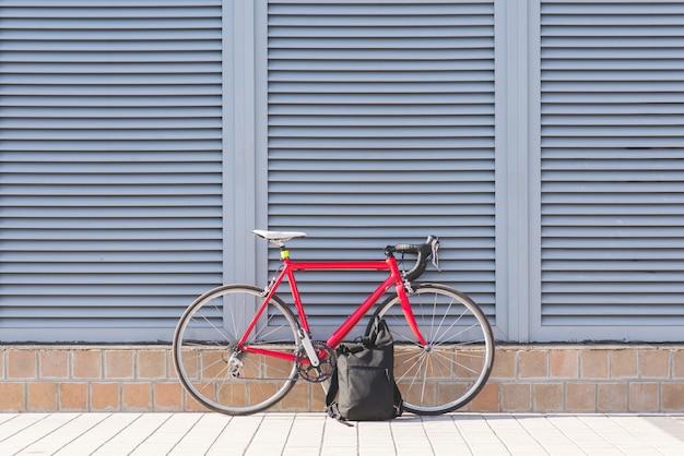 Rode racefiets en rugzak tegen een grijze muur