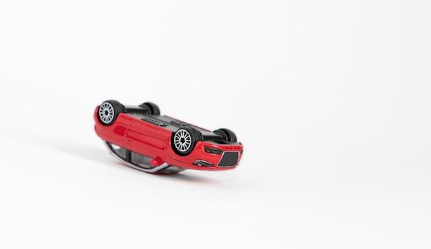 Rode rammelaar speelgoedauto, omgedraaid op het dak als gevolg van een ongeval.