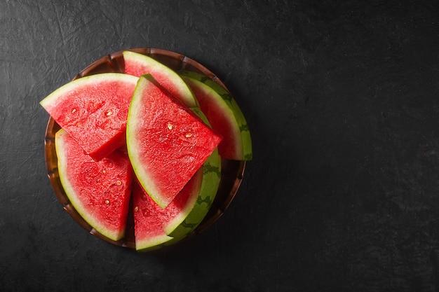 Rode rauwe watermeloen stukken op donkere achtergrond, bovenaanzicht. het is zoet, sappig vruchtvlees, meestal dieprood tot roze, met veel zwarte zaden, hoewel er ook pitloze varianten bestaan