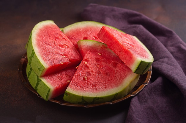 Rode rauwe watermeloen stukken op donkere achtergrond
