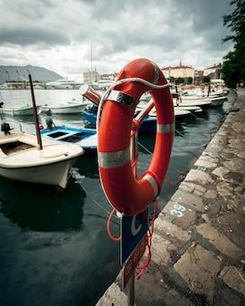 Rode reddingsboei hangend in zeehaven op regenachtige dag