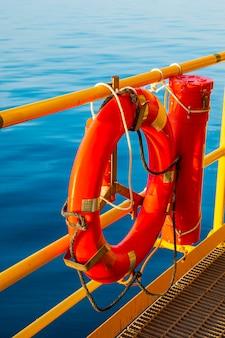 Rode reddingsboei op een tuig voor de kust in de zee.