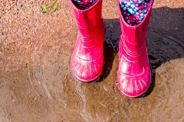 Rode regenlaarzen, springend in een plas. felrode rubberen laarzen voor kinderen