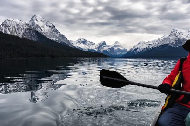 Rode reizigers kanovaren en rotsachtige berg in maligne-meer
