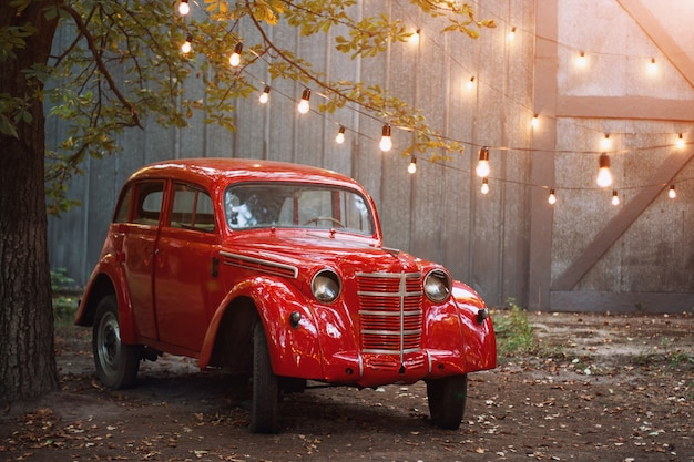 Rode retro auto die zich in de tuin in de zomer op een grijze muur en brandende bollen bevinden. vintage voertuig in de buurt van de garage versierd met lichtslinger.