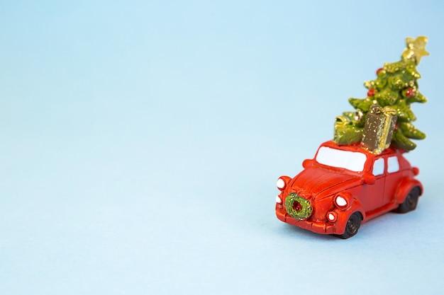 Rode retro auto draagt een kerstboom met geschenkdozen op het dak