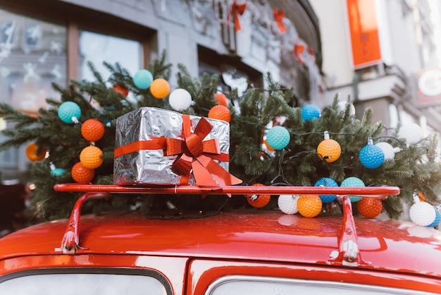 Rode retro auto met een kerstboomspar die aan het dak wordt gebonden, het symbool van de familiefeest.