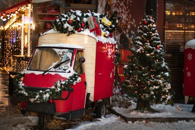 Rode retro bestelwagen versierd voor kerstmis met een kerstboom op het dak en een dennenboom versierd met speelgoed