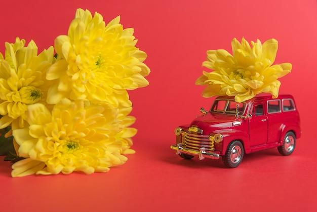 Rode retro speelgoedauto die een boeket van gele chrysantenbloemen levert op een rode achtergrond. bloemen levering.