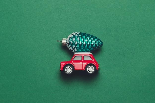 Rode retro speelgoedauto met kerstmis of nieuwjaar speelgoed van de leveringskerstmis op een groene achtergrond