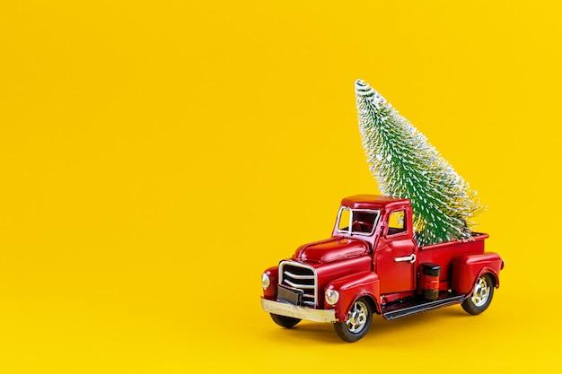 Rode retro stuk speelgoed vrachtwagen met kerstboom op vrachtwagenlichaam op gele muur. levering, kerstmis, nieuwjaar concept. vintage speelgoed modelauto met kerstboom kopieer de ruimte.