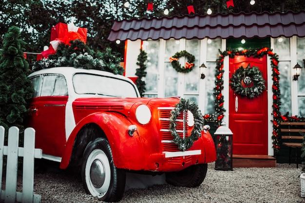 Rode retro vintage auto in feestelijke decoraties. vrolijk kerstfeest.
