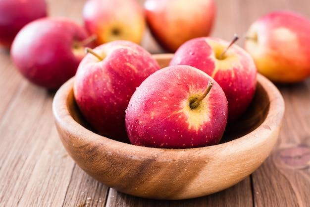 Rode rijpe appels in een houten plaat en op een houten tafel