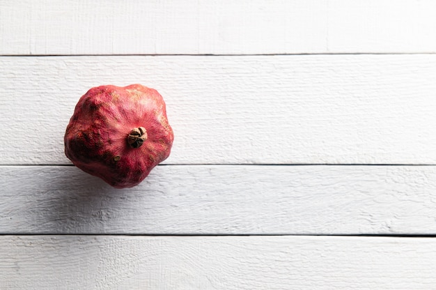Rode rijpe granaatappel op houten witte plank achtergrond