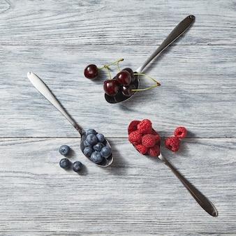 Rode rijpe sappige bessen - kersen en frambozen, bosbessen in de drie metalen lepels en in de buurt van hen op een grijze houten achtergrond. bovenaanzicht Premium Foto
