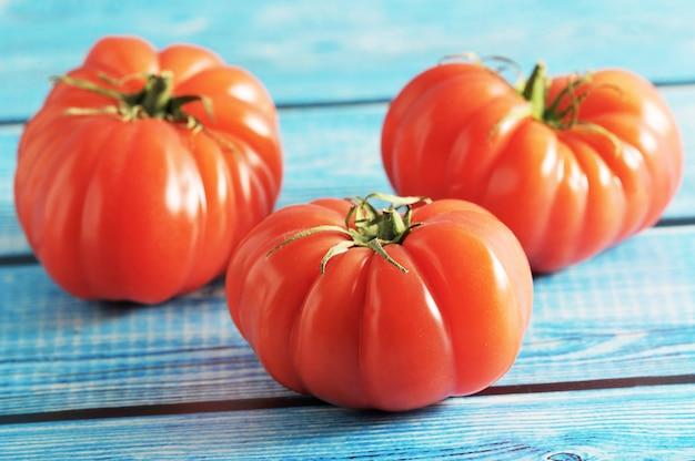 Rode rijpe tomaat drie met groene steel op een blauwe achtergrond