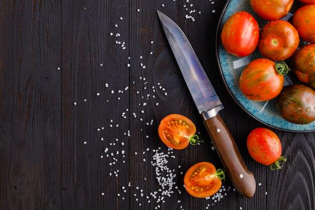 Rode, rijpe tomaten op een donkere achtergrond. tomaten oogsten. bovenaanzicht. kopieer ruimte
