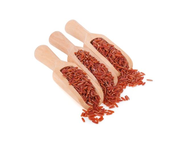 Rode rijst in een houten kom die op witte achtergrond wordt geïsoleerd