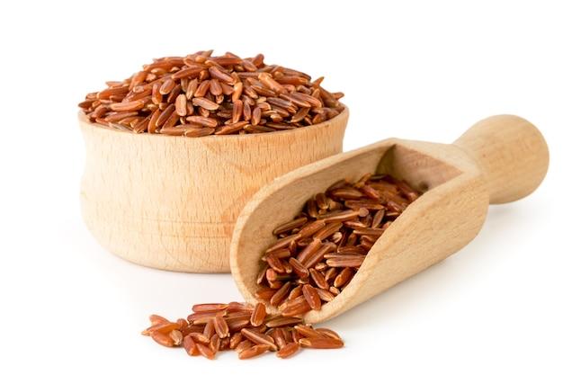 Rode rijst in houten geïsoleerde plaat en lepel