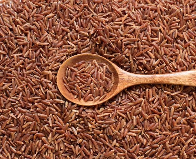 Rode rijst met een houten lepel