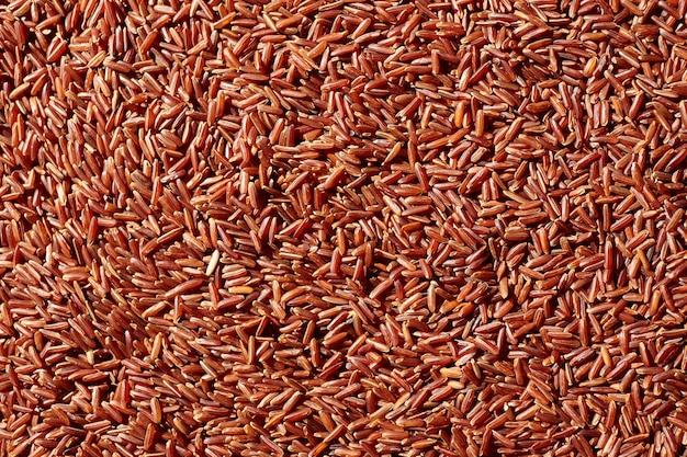 Rode rijst textuur achtergrond. ongekookte droge granen