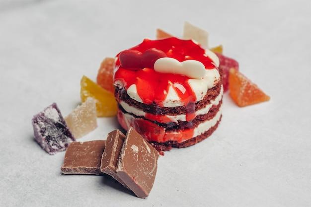 Rode ronde cake op een plaat snoepjes snoep dessert snack kopje thee