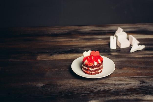 Rode ronde cake snoep maaltijd dessert met thee houten achtergrond