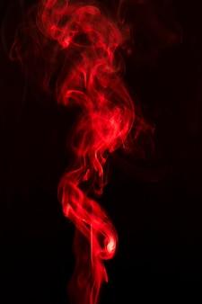 Rode rook die tegen zwarte achtergrond wervelt