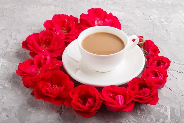 Rode roos bloemen in een spiraal en een kopje koffie op grijs beton