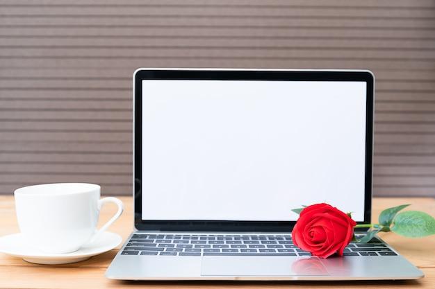 Rode roos en koffiekopje met laptop mockup op hout achtergrond, valentijn concept