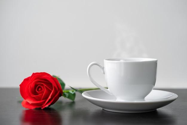 Rode roos en koffiekopje op de houten tafel agent witte achtergrond, valentijn concept