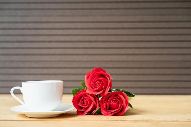 Rode roos en koffiekopje op hout achtergrond, valentijn concept