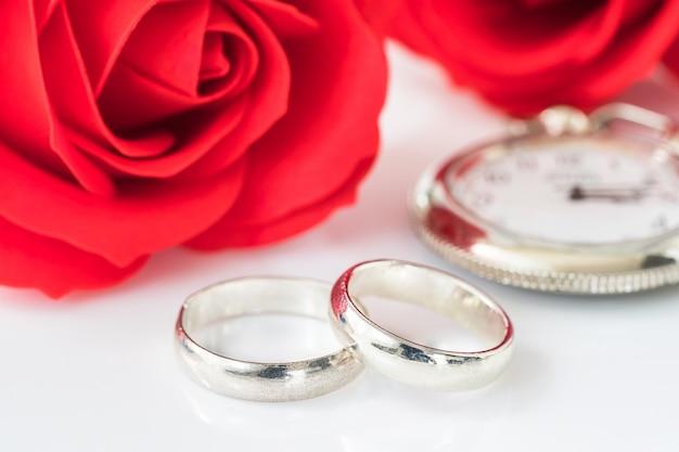 Rode roos en trouwring op wit