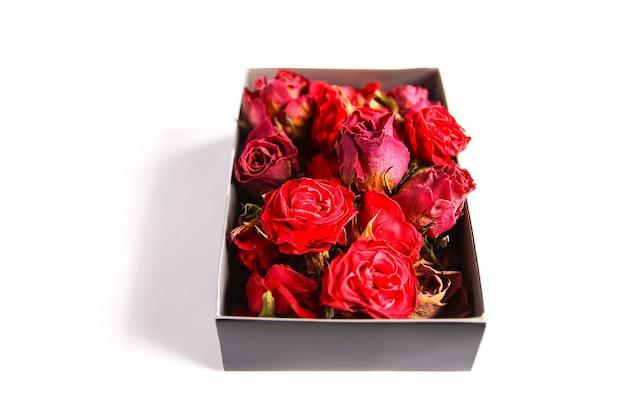 Rode roos gedroogde knoppen, bloemen en bloemblaadjes in de geopende kartonnen doos