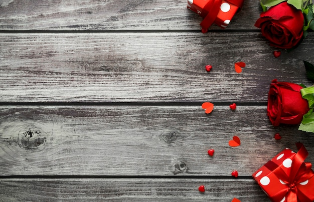 Rode roos, geschenkdoos en hart op houten achtergrond met kopie ruimte voor tekst. bovenaanzicht valentijn dag concept.