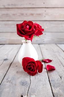 Rode roos in vaas op houten tafel