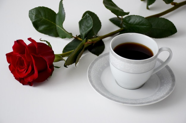 Rode roos, kopje thee op plaat van grijze theeset op witte tafel. valentijnsdag koffie