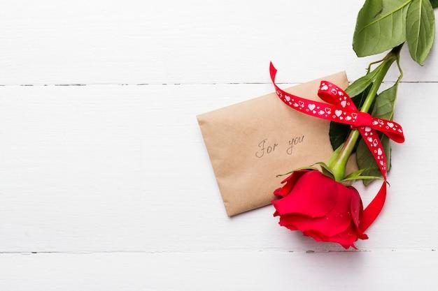 Rode roos, liefde bericht op een witte houten achtergrond