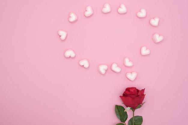 Rode roos met bellen spraakharten op roze papier achtergrond