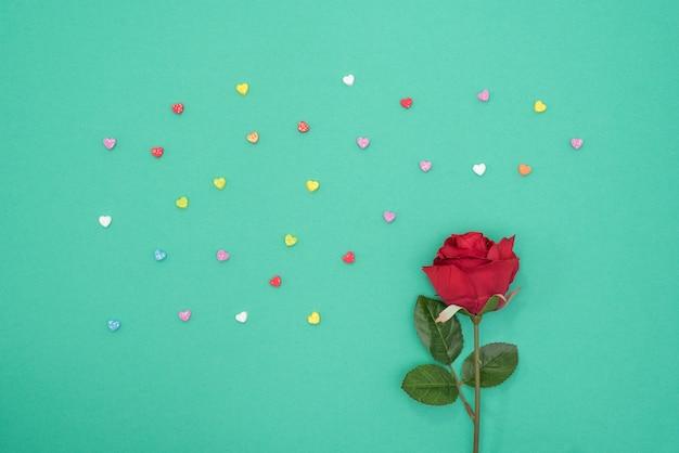 Rode roos met glitter harten op groene papier achtergrond