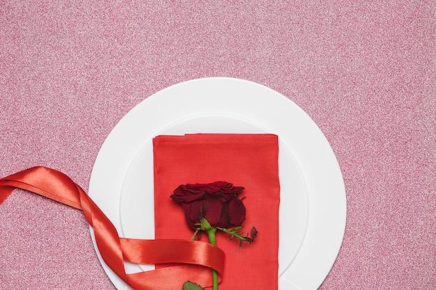 Rode roos met lint op plaat op rode achtergrond. valentijnsdag.