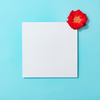 Rode roos op pastelblauw met papieren kaartnota